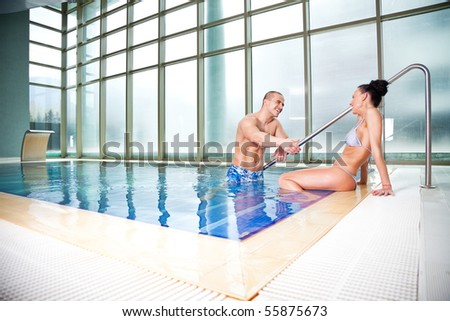 Young attractive couple chatting and playing in a swimming pool