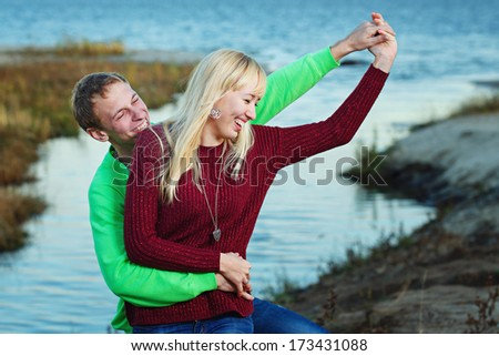 Young attractive couple embracing on the riverbank fall day - stock photo