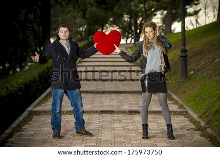 young attractive couple fighting over a love hearted shaped pillow  - stock photo