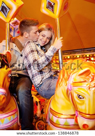 Young attractive couple having fun and riding horses together on a colorful carousel at an amusement attractions arcade ground with multiple lights in the background at night time.