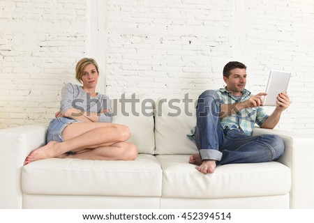 young attractive couple husband and wife at home living room couch with happy man using internet app on digital tablet pad ignoring bored and sad woman in social network addiction concept - stock photo