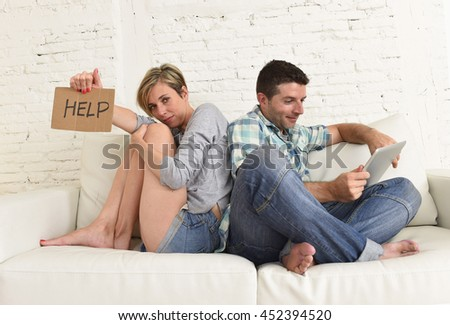 young attractive couple husband and wife at home living room couch with happy man using internet digital tablet pad in social network addiction concept ignoring bored sad woman asking for help - stock photo