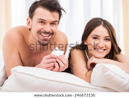 Young attractive couple in bed with a condom. - stock photo