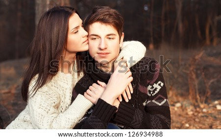 Young attractive couple in love kissing on the beach in evening. Cold weather, soft sunny colors. - stock photo