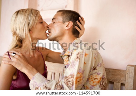 Young attractive couple intensely kissing while sitting down on a bench on honeymoon. - stock photo