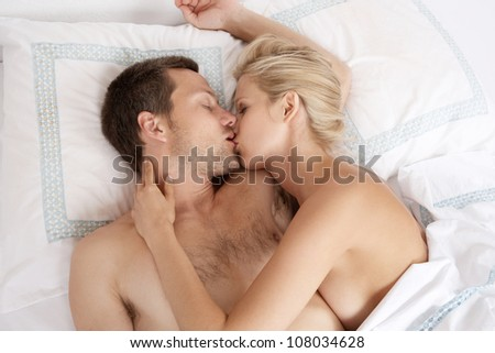 Young attractive couple kissing in bed. - stock photo