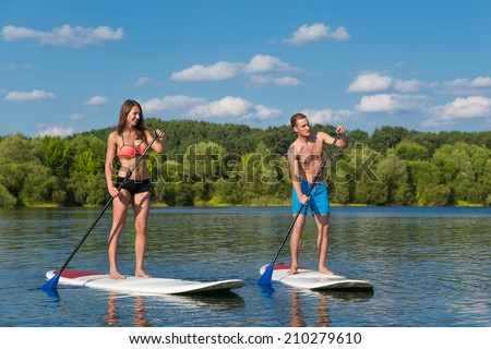 Young attractive couple on stand up paddle board in the lake, SUP - stock photo