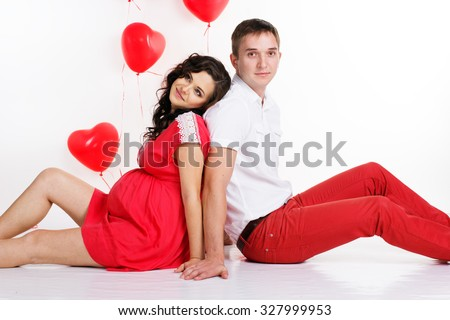 Young attractive couple: pregnant girl and her boyfriend are wearing red fashion clothes with red heart shape balloons isolated on white in studio