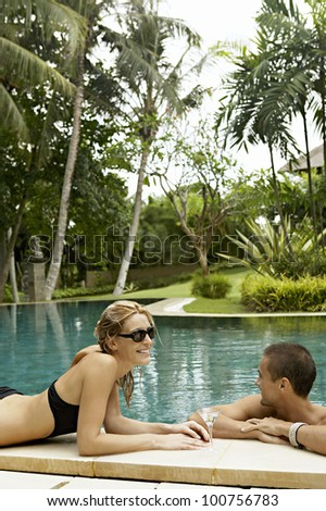 Young attractive couple relaxing by a swimming pool in a tropical garden.
