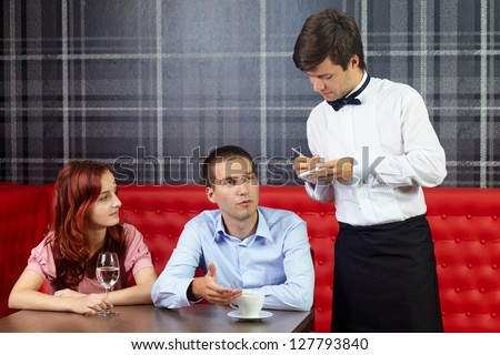 Young attractive couple sitting in restaurant and talking to handsome waiter - stock photo