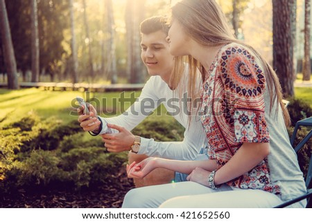 Young attractive couple sitting on a bench in a park and using smartphone. - stock photo