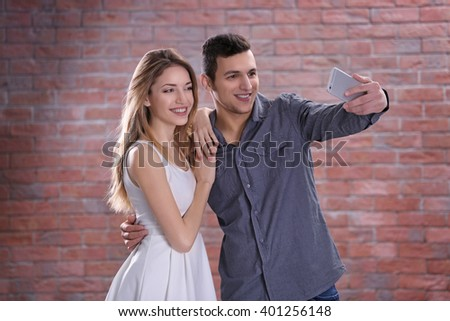 Young attractive couple taking selfie with mobile phone on brick wall background - stock photo