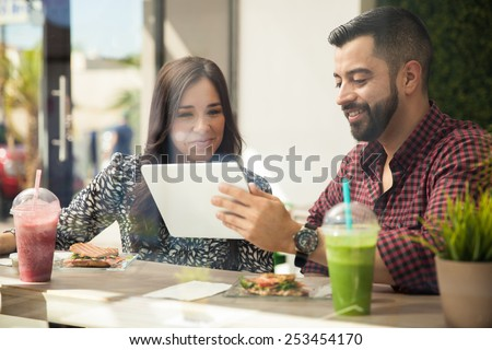 Young attractive couple using a tablet computer while eating a healthy lunch at a cafe - stock photo