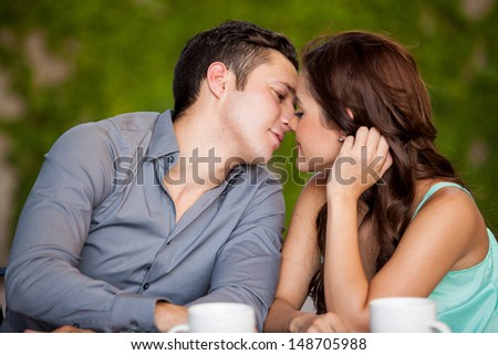 Young attractive couple very close to kissing each other while on their date at a cafe - stock photo