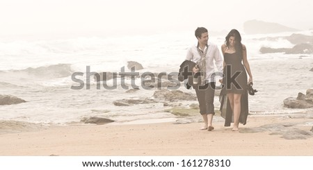 Young attractive couple walking along misty beach  - stock photo