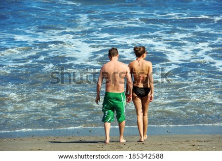 Young attractive couple walking on a beach  - stock photo