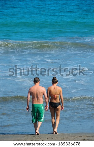Young attractive couple walking on a beach (your text on top of the image) - stock photo