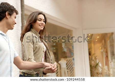 Young attractive couple walking past shop windows in town while holding hands, smiling.