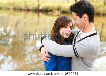 Young attractive couple who are in love spending a happy day together in the park near a river stream in winter - stock photo