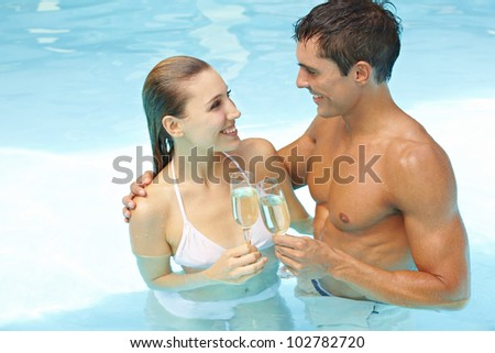 Young attractive couple with champagne in swimming pool - stock photo