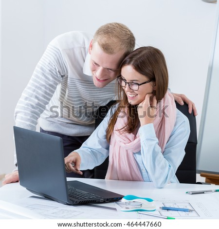 Young attractive couple working together in office