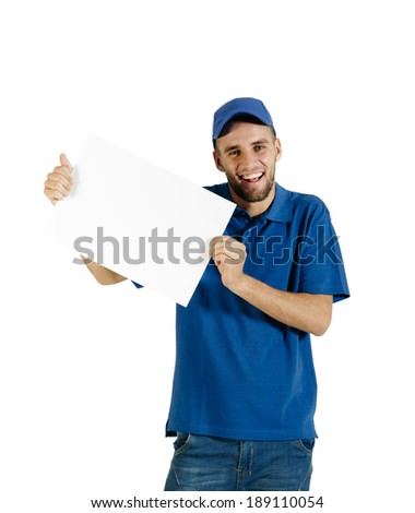 Young attractive courier guy holding white place card - stock photo