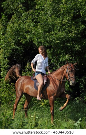 Young attractive cowgirl galloping horseback in country road