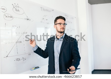 Young attractive dark-haired man in glasses is showing a business plan on whiteboard. He wears blue shirt and dark jacket.