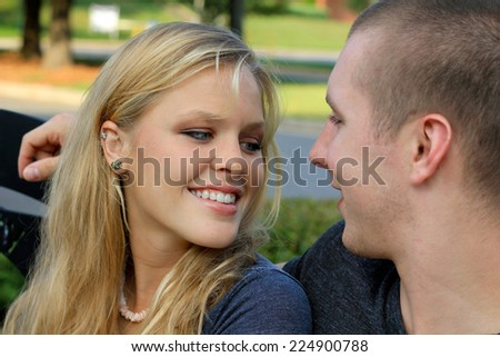 Young Attractive Dating Couple Happy in Love Blonde Boyfriend with Arm Around Girlfriend Smiling Friendly Looking at Each Other  - stock photo