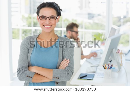 Young attractive designer smiling at camera in creative office - stock photo
