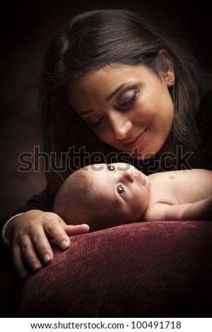 Young Attractive Ethnic Woman Holding Her Newborn Baby Under Dramatic Lighting. - stock photo