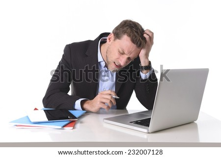 young attractive European businessman working in stress at office desk computer laptop suffering headache, worried and frustrated isolated on white background - stock photo