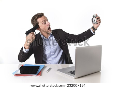 young attractive European businessman working in stress at office desk computer pointing gun to head holding watch in overwork and overtime work concept - stock photo