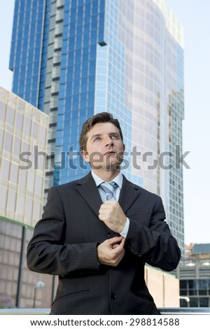 young attractive executive businessman adjusting shirt cuff link standing outdoors in financial district dressing for success in the city