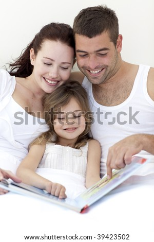 Young attractive family reading together in bed