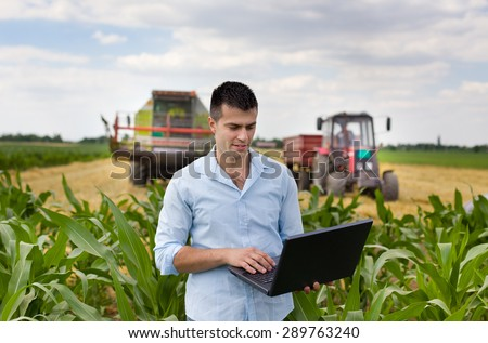 Young attractive farmer with laptop standing in corn field, tractor and combine harvester working in wheat field in background - stock photo