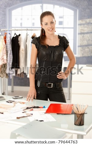 Young attractive fashion designer standing by desk in office, smiling.? - stock photo
