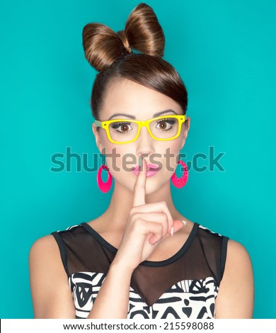 Young attractive fashionable woman with finger on lips, secret concept - stock photo