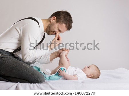Young attractive father is changing nappy to his baby girl - stock photo