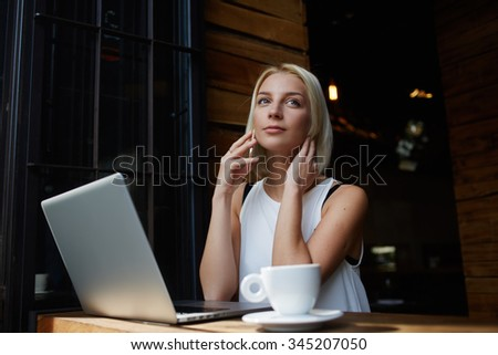 Young attractive female calling with her smart phone while sitting with portable net-book in coffee shop, beautiful blonde female talking on cell telephone while rest after work on laptop computer  - stock photo