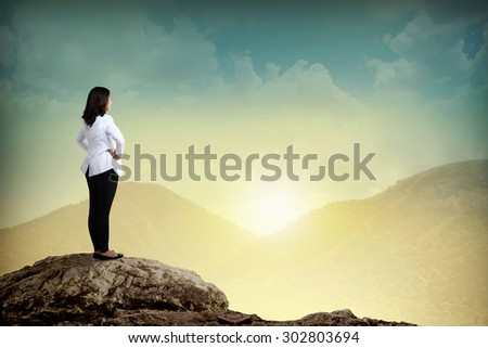 Young attractive female doctor standing on the mountain - stock photo