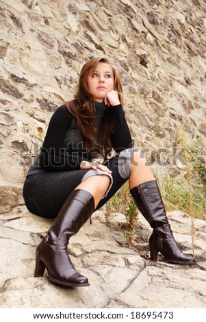 young attractive female dressed in grey pullover posing in front of old wall - stock photo