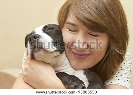 Young attractive female embracing her Pit Bull puppy - stock photo