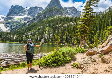 Young attractive female enjoying stunning view at lake Odessa with notchtop peak in rocky mountain national park colorado - stock photo