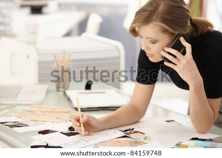 Young attractive female fashion designer working at office desk, drawing while talking on mobile.? - stock photo