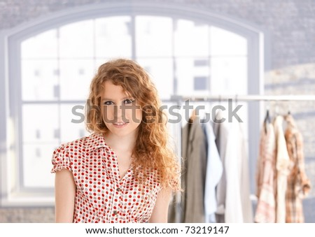 Young attractive female fashion designer working in office at desk smiling.? - stock photo