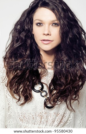 Young attractive female fashion model with long curly hair.