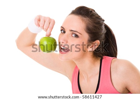 young attractive female in fitness top eats green apple, studio shoot isolated on white - stock photo