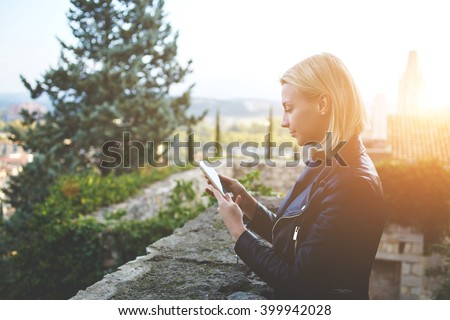 Young attractive female is reading text message in social network via mobile phone during her walking tour outside. Hipster girl is chatting with friends via cellphone during recreation time outdoors  - stock photo