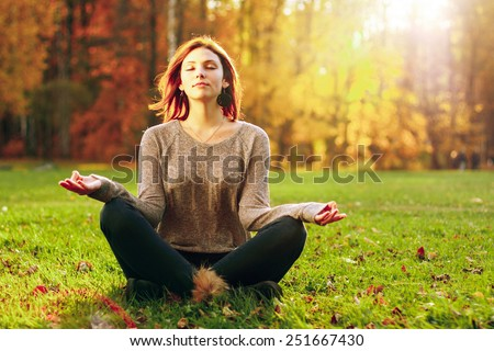 Young attractive female meditate in park. Outdoor shot - stock photo